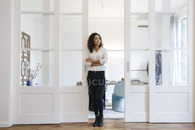 Бізнес-леді стоячи в офіс і дивиться вбік — стокове фото
