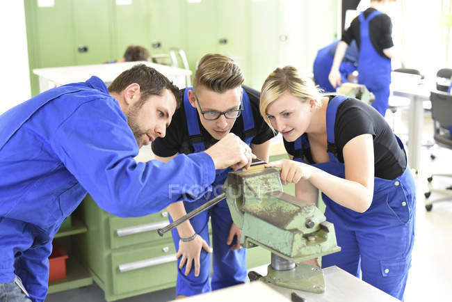 Instructor with trainees at workbench — Stock Photo