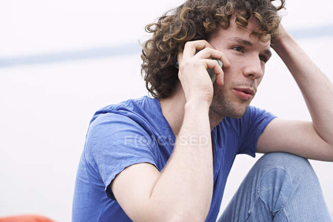Young man sitting and talking on the phone — Stock Photo