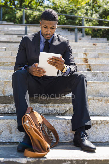 Uomo d'affari seduto sulle scale utilizzando tablet — Foto stock