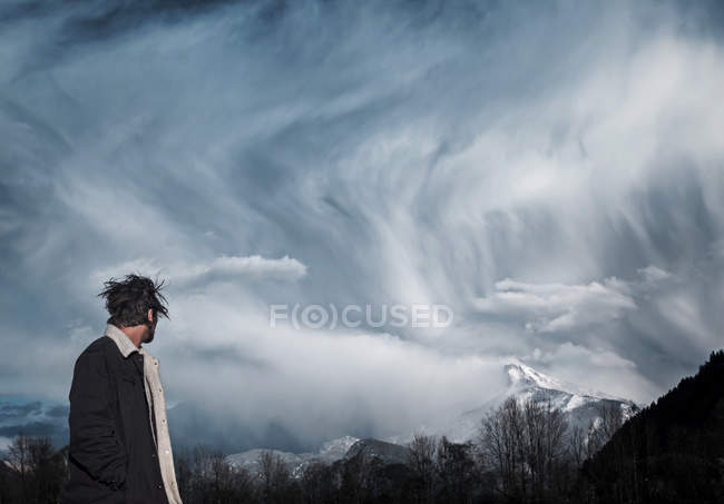 Side portrait of man looking at cloudscape over mountains — Stock Photo