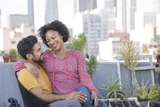 Пара сидящая на крыше, Лос-Анджелес, США — стоковое фото