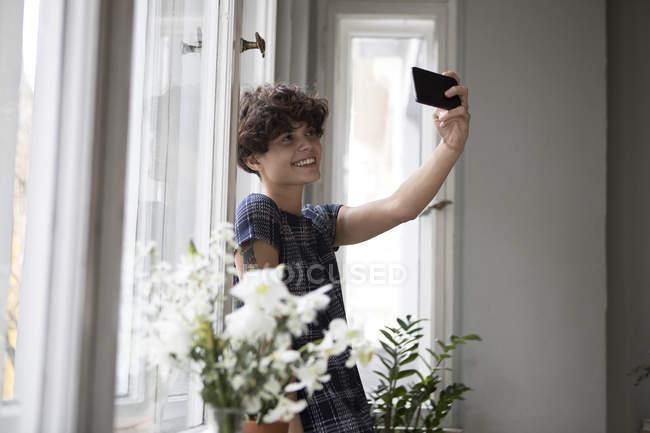 Улыбающаяся молодая женщина стоит перед окном и делает селфи со смартфоном — стоковое фото