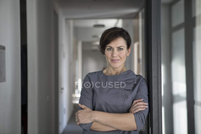 Portrait of confident businesswoman standing with arms crossed — Stock Photo