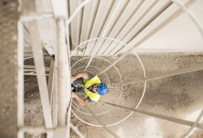 Worker climbing up stairs on factory, high angle — Stock Photo