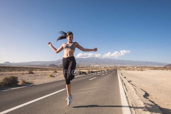 Esportiva jovem mulher pulando na estrada vazia — Fotografia de Stock