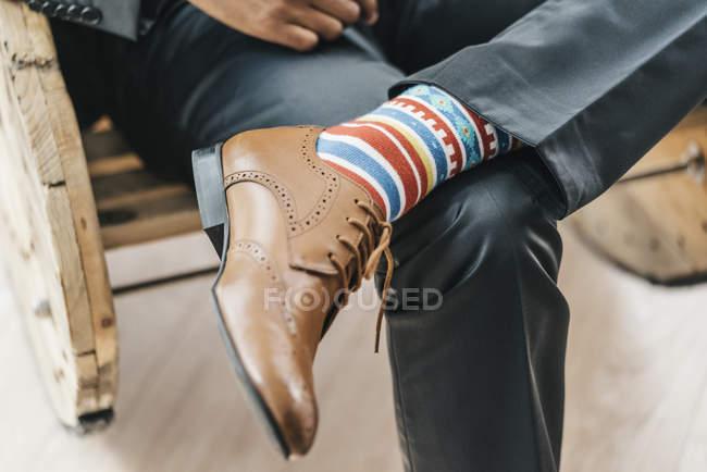 Крупный бизнесмен, сидя со скрещенными ногами — стоковое фото