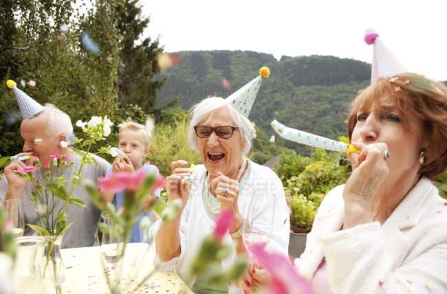 Seniors celebrating birthday oarty in garden — Stock Photo