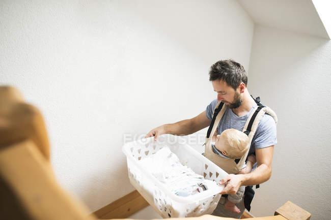 Отец с ребенком в детское перевозчика, ходьба наверху с корзину Прачечная — стоковое фото