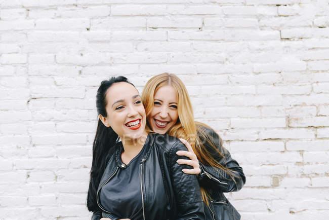 Deux jeunes femmes riantes devant un mur de briques blanches — Photo de stock