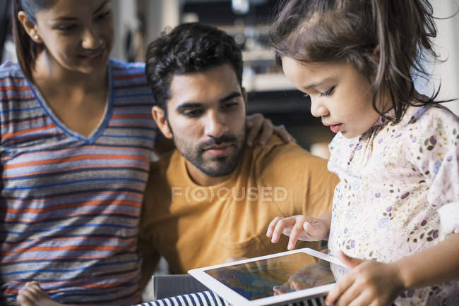 Parents with daughter looking at digital tablet at home — Stock Photo