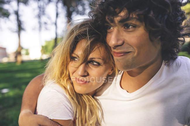Улыбающаяся молодая пара, обнимающаяся в парке — стоковое фото