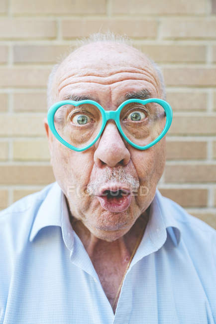 Portrait of senior man wearing heart-shaped glasses pulling funny faces — Stock Photo