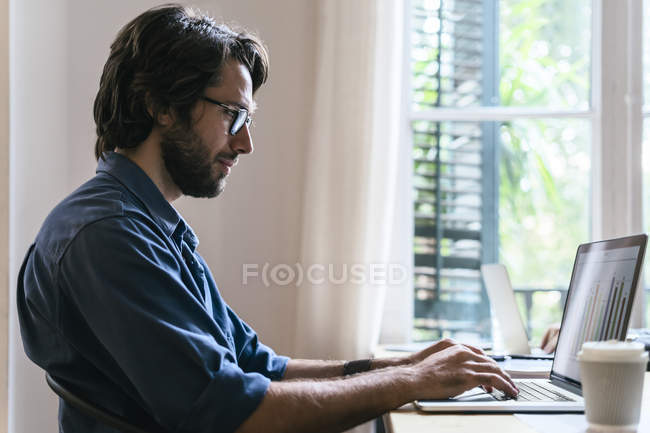 Businessman sitting in office and working on laptop — Stock Photo