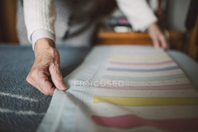 Senior woman putting fresh sheets on a bed — Stock Photo