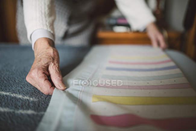 Seniorin legt frische Bettwäsche aufs Bett — Stockfoto