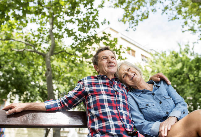 Happy cute senior couple sitting together on bench and hugging at park — Stock Photo
