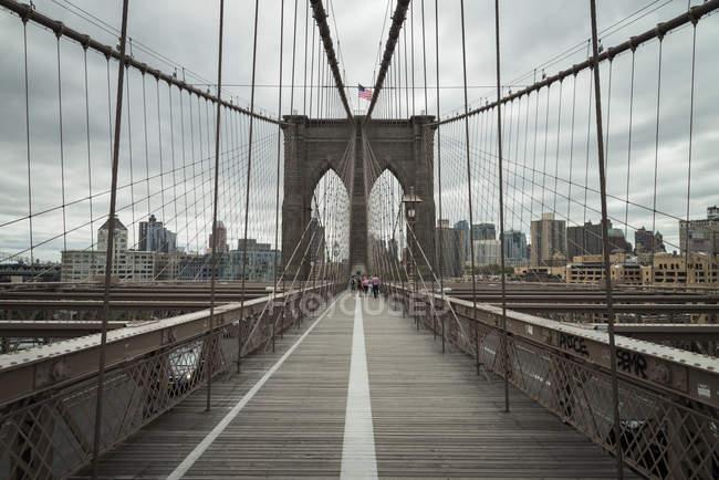 États-Unis, New York, passerelle piétonne sur Brooklyn Bridge et paysage urbain en arrière-plan — Photo de stock