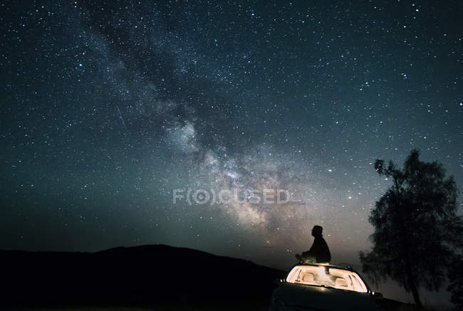 Distant view of starry sky with man sitting on car roof — Stock Photo