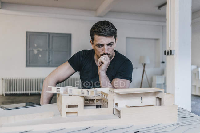 Architect looking at architectural model in workshop — Stock Photo