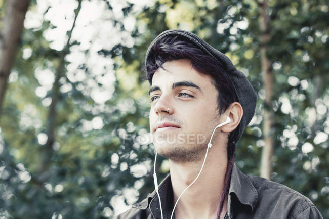 Portrait of smiling young man with cap listening music with earphones — Stock Photo