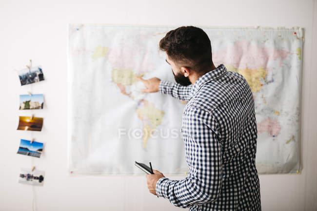 Молодой человек, выбор туристических направлений на карте мира — стоковое фото