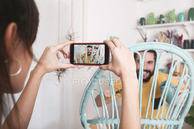 Young woman taking photo of bearded man painting wicker armchair at home — Stock Photo