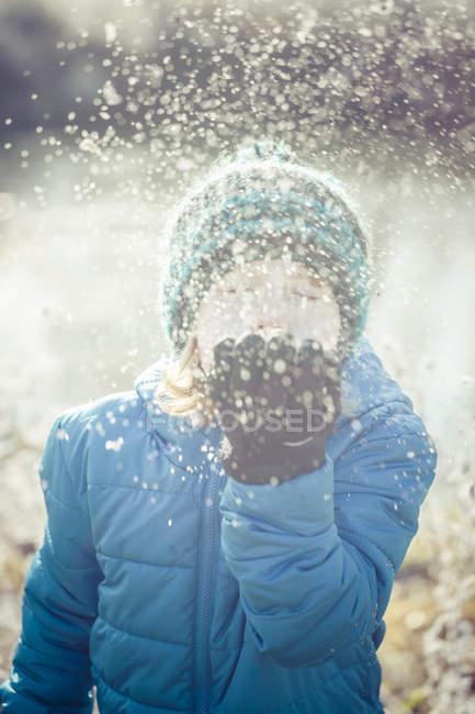 Primo piano di ragazzo soffiando neve all'aperto — Foto stock