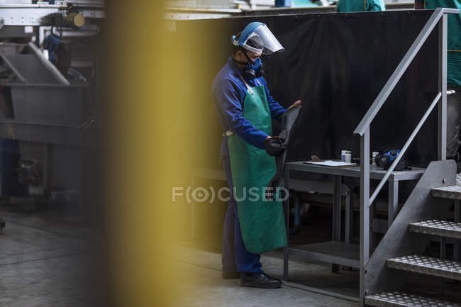 Worker wearing protective mask in factory — Stock Photo