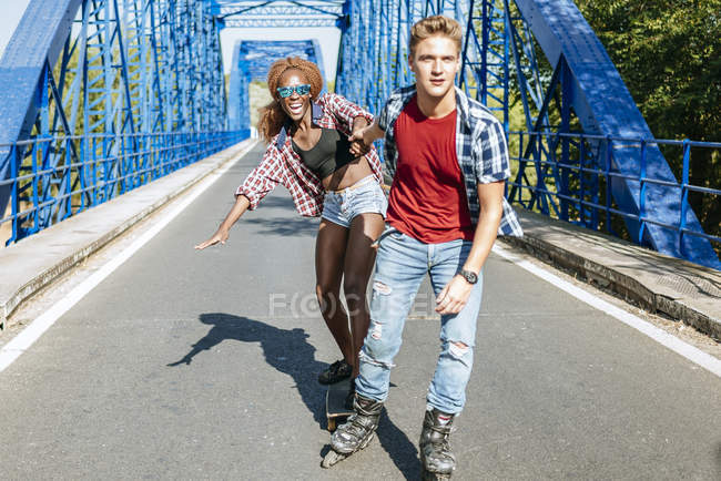 Young couple with inline skates and skateboard riding on bridge — Stock Photo
