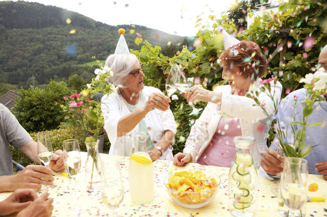 Group of seniors celebrating, drinking champagne — Stock Photo