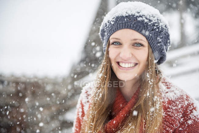 Portrait of smiling young woman in heavy snowfall — Stock Photo