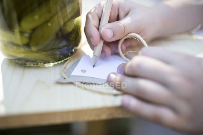 Fille écriture sur l'étiquette à côté de pot avec des cornichons conservés — Photo de stock