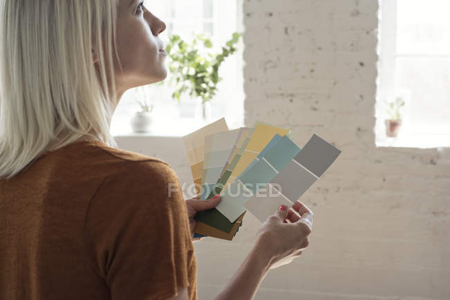 Young woman in a loft thinking about color samples — Stock Photo