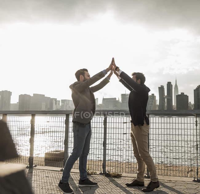 Zwei Geschäftsleute geben hohe fünf am East River in New York City, Usa — Stockfoto