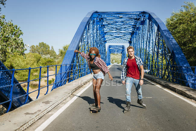 Young couple with inline skates and skateboard riding on a bridge — Stock Photo