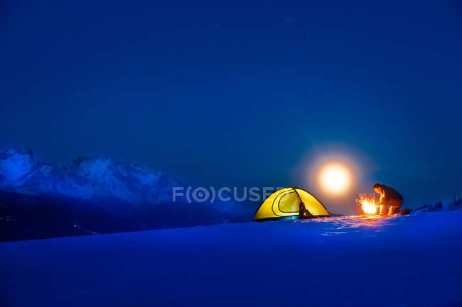 Senior woman camping im tief verschneiten Landschaft bei Vollmond — Stockfoto