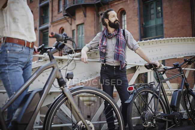 Freigeschnittenes Porträt eines Paares, das mit Fahrrädern auf Brücke steht — Stockfoto