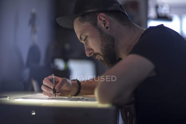 Close-up of Graphic artist sketching in dark room — Stock Photo