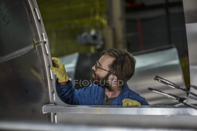 Man inspecting steel container in factory — Stock Photo