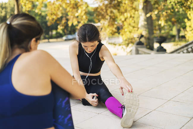 Two sportive young women sitting and stretching in park — Stock Photo