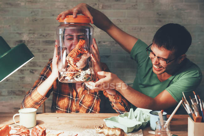 Young couple having fun with animal figurines in jar — Stock Photo