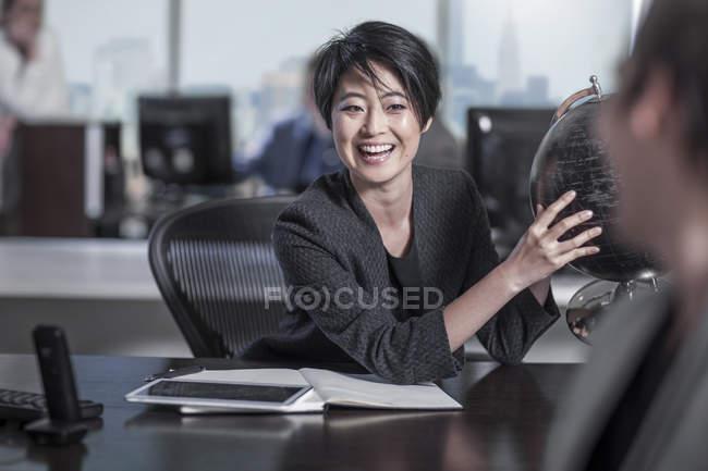 Нью-Йорк office, азіатські жінки в бюро з глобус Землі в Міський офіс — стокове фото