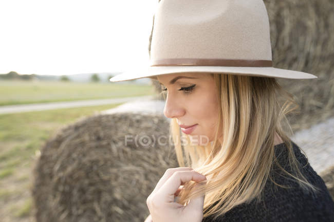 Young woman with hat in rural landscape — Stock Photo