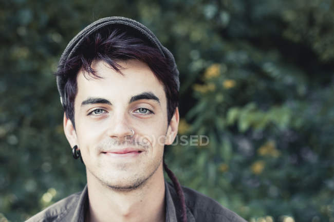 Portrait of smiling young man with nose piercing and earring wearing cap — Stock Photo
