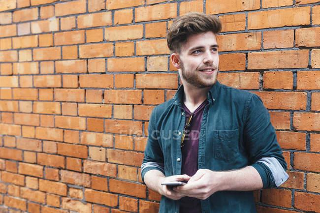 Счастливый молодой человек со смартфоном на фоне сломанной стены — стоковое фото