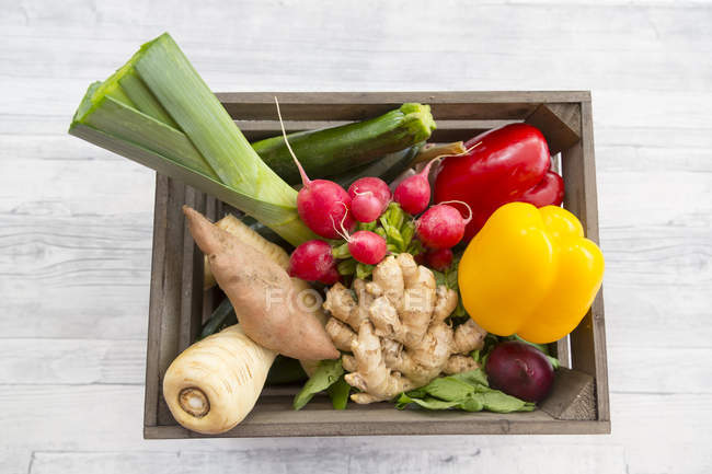 Wooden box with fresh vegetables on white wood surface — Stock Photo