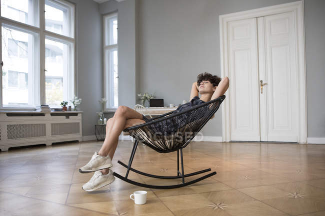 Young woman relaxing on rocking chair at home — Stock Photo