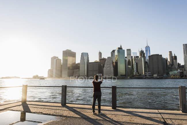 Frau unter Bild der Skyline von Manhattan — Stockfoto
