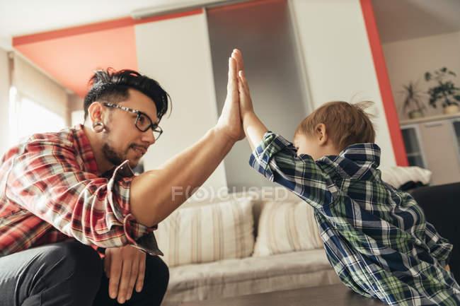 Батько і син, надаючи висока п'ять вдома — стокове фото